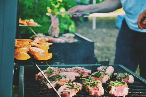 男性がBBQコンロで肉を焼いている様子