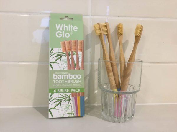 竹製の歯ブラシがグラスに立てかけられている様子