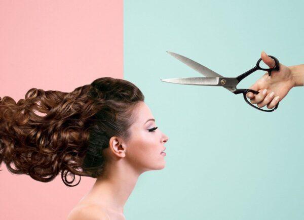 女性が裁断バサミで髪の毛を切られる様子