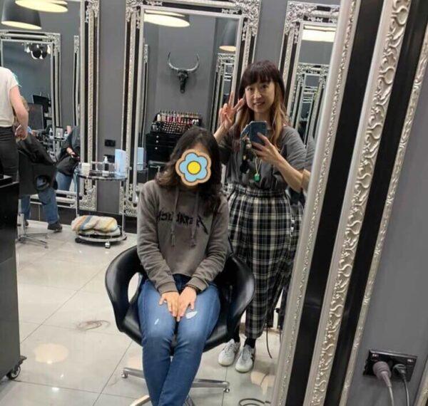 美容師さんと一緒に鏡越しに写真撮影している様子