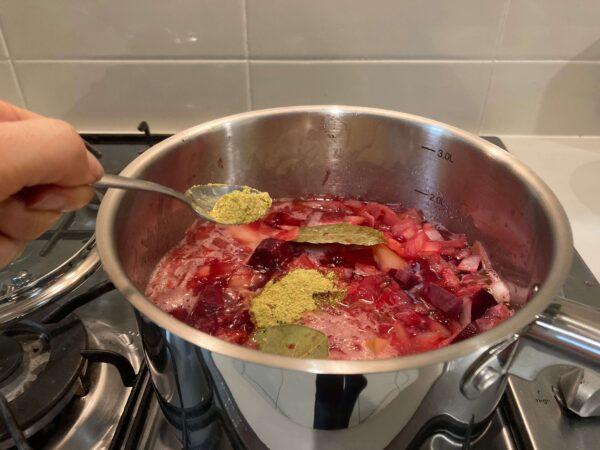 煮込んだ野菜にスープストックを加える様子